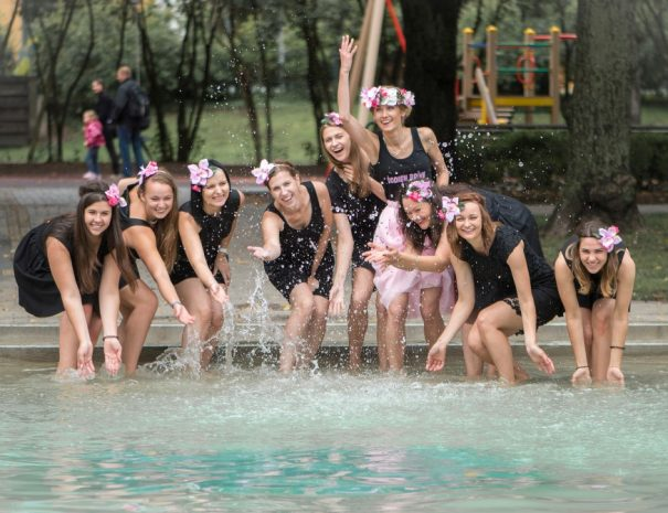 millennial-women-celebtating-an-event-at-the-pool-in-pink-and-black-outfit-in-summer-splashing-water_t20_ax7bAw